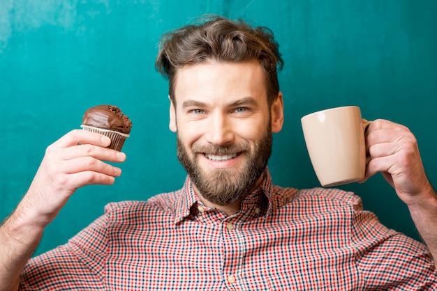 緑の背景にチョコレートマフィンとコーヒーカップを持つ男のクローズアップの肖像画
