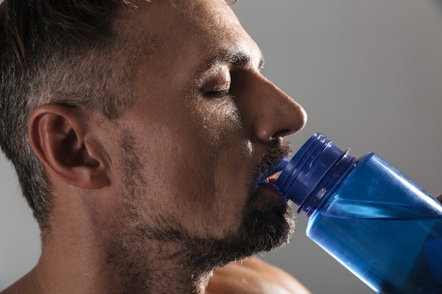 成熟した上半身裸のスポーツマン飲料水の肖像画を間近します。