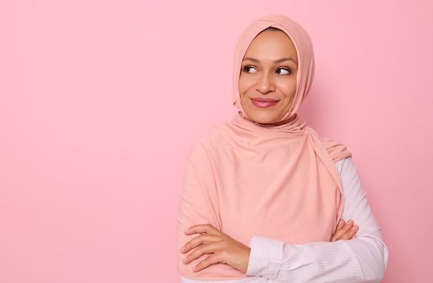 コピースペースと思慮深く笑っているピンクの背景の側面を不思議に見ているヒジャーブで覆われた頭を持つ中年のアラブのイスラム教徒のかなりゴージャスな女性のクローズアップの肖像画