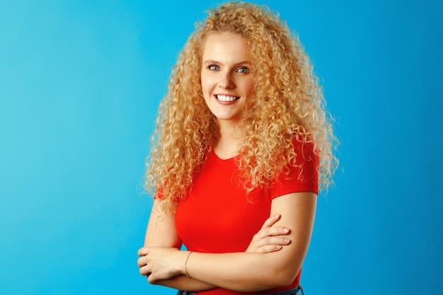 長い巻き毛の素敵な若い女性の肖像画をクローズアップ、スタジオショット