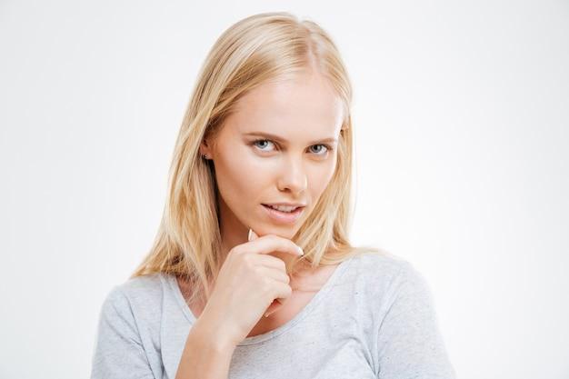 파란 벽에 고립된 무언가에 대해 생각하고 있는 생각에 잠긴 아름다운 금발 소녀의 클로즈업 초상화