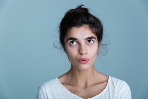 青い背景の上に孤立して立っている白いtシャツを着て物思いにふける不満のかなり若いブルネットの女性の肖像画をクローズアップ