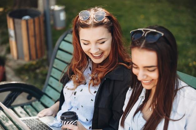 밖에 서 웃고 벤치에 앉아있는 동안 그녀의 친구 태블릿을 내려다보고 빨간 머리를 가진 더하기 크기 여성의 초상화를 닫습니다.