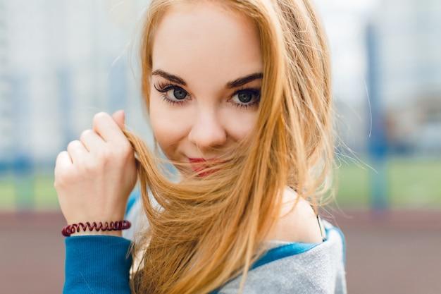 スタジアムに立っているかわいい女の子のクローズアップの肖像画。彼女は髪の毛が長く、カメラに微笑んでいます。