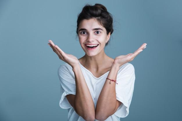 青い背景の上に孤立して立っている白いtシャツを着て、カメラを見て、かなり笑顔の若いブルネットの女性の肖像画をクローズアップ