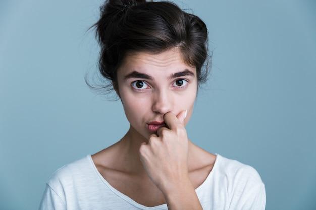 青い背景の上に孤立して立って、ポーズをとって、顔に触れて白いtシャツを着ているかなり若いブルネットの女性の肖像画をクローズアップ