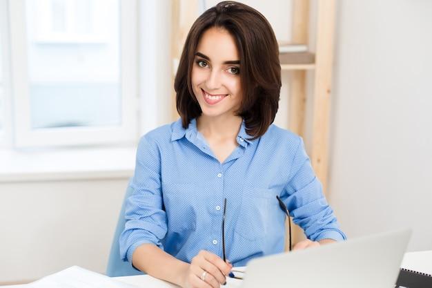 青いシャツを着たかなり若い女の子のクローズアップの肖像画。彼女はオフィスのテーブルに座って、カメラに微笑んでいます。