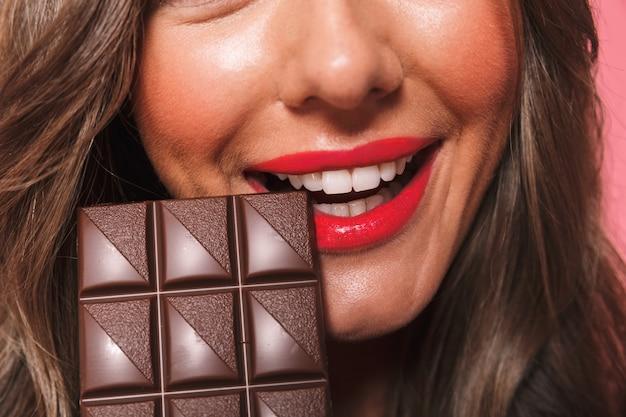 チョコレートを食べるかなり若い女性の肖像画を間近します。