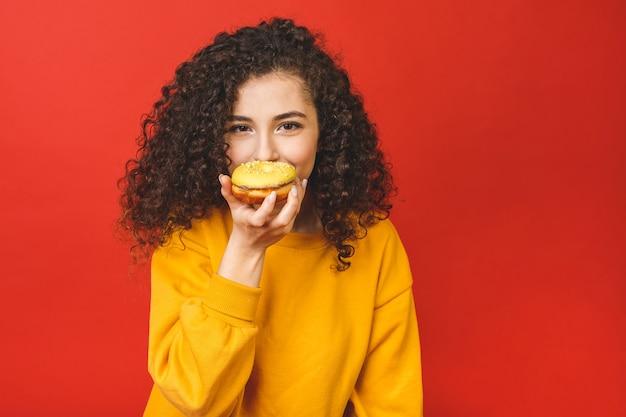 赤い背景の上に孤立したドーナツを食べて満足してかなり若い女の子の肖像画を間近します。
