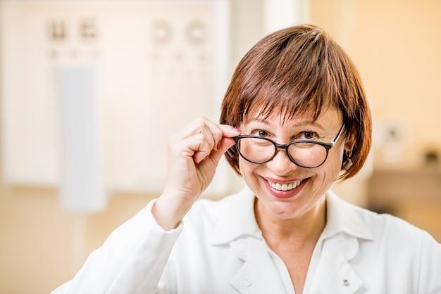 眼科医院で眼鏡をかけている制服を着た年配の女性医師のクローズアップの肖像画