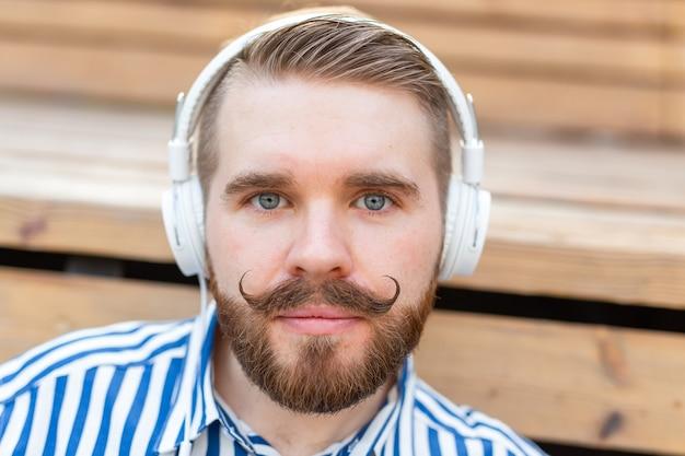 彼のお気に入りのオンラインラジオを使用して聞いている真面目な若い学生の男のクローズアップの肖像画