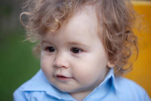 小さな金髪の男の子の肖像画をクローズアップ。面白い子供たちの顔。