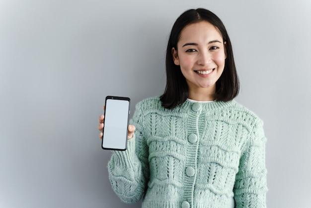Крупным планом портрет улыбающейся азиатской женщины, показывающей пустой экран мобильного телефона