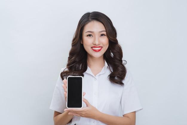 Крупным планом портрет улыбающейся азиатской женщины, показывающей пустой экран мобильного телефона, стоя изолированной на сером фоне
