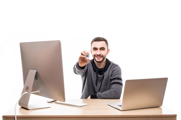 Крупным планом портрет улыбающегося предпринимателя, держащего биткойн, сидя за столом с ноутбуком и компьютером, изолированным на белом