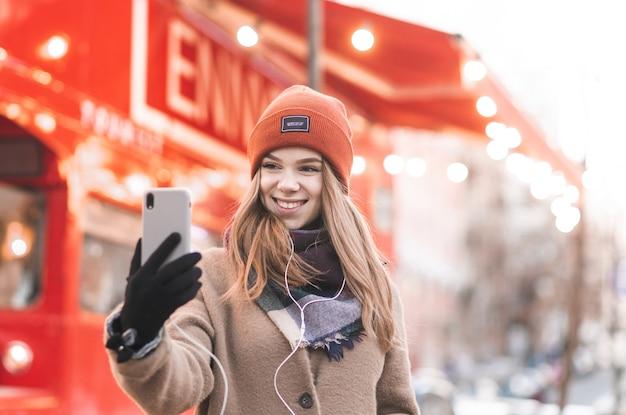 暖かい服を着て微笑んでいる女の子のクローズアップの肖像画は、明るい赤い街の背景を持つスマートフォンでselfieを取る