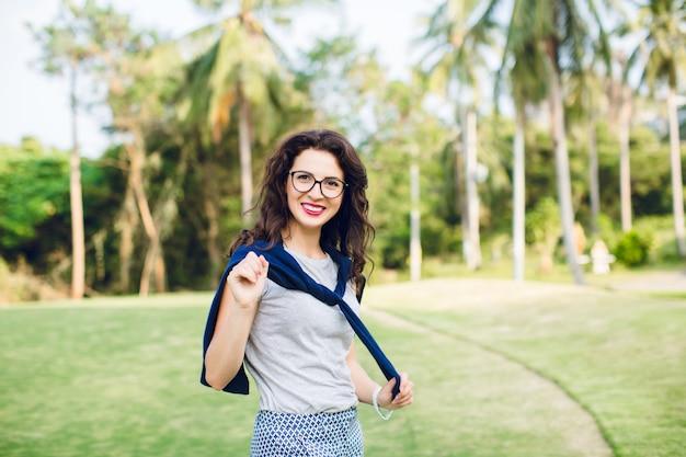 暗い短い髪と黒いメガネで微笑んでいる女の子のクローズアップの肖像画