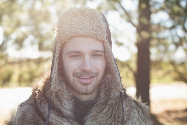 Закрыть портрет улыбающегося человека в теплую одежду в лесу