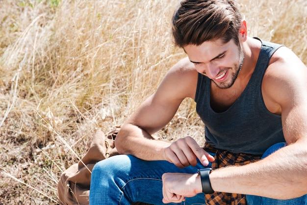 야외에서 쉬고 스마트 시계를 사용하여 웃는 젊은 남자의 초상화를 닫습니다