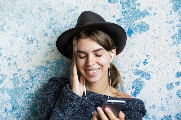 Крупным планом портрет улыбающейся молодой женщины, одетой в шляпу и свитер, слушающей музыку с наушниками, держа мобильный телефон над синей стеной