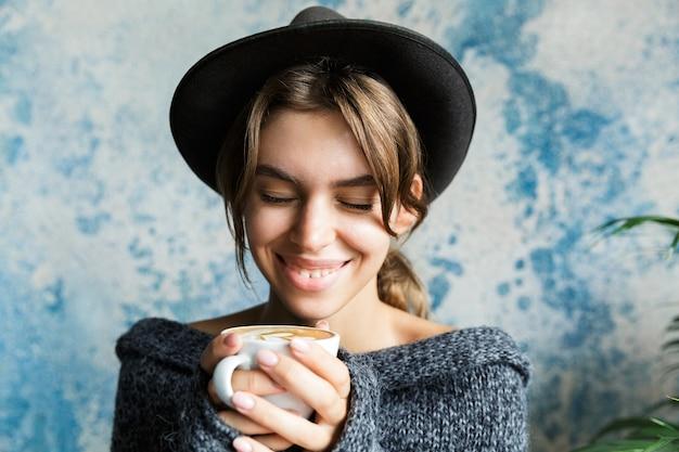 뜨거운 커피 한잔 들고 파란색 벽에 스웨터와 모자를 입고 웃는 젊은 여자의 초상화를 닫습니다