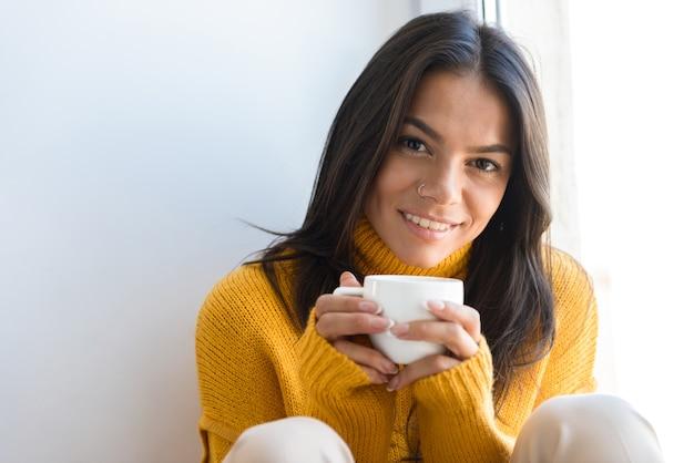 お茶を持って、屋内の窓に座ってセーターを着て笑顔の若い女性の肖像画をクローズアップ