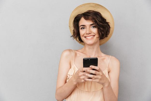 夏の帽子の笑顔の若い女性の肖像画を閉じる