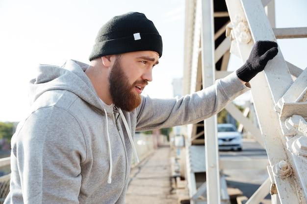 帽子をかぶって外で休んでいるスポーツマンの肖像画をクローズアップ