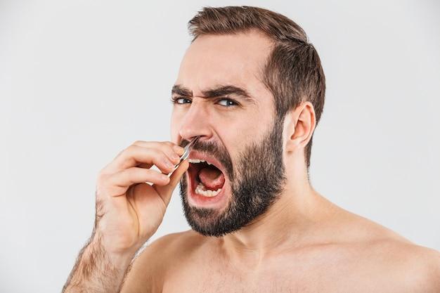Крупным планом портрет страдающего бородатого мужчины, стоящего изолированно над белой и выщипывающего волосы из носа