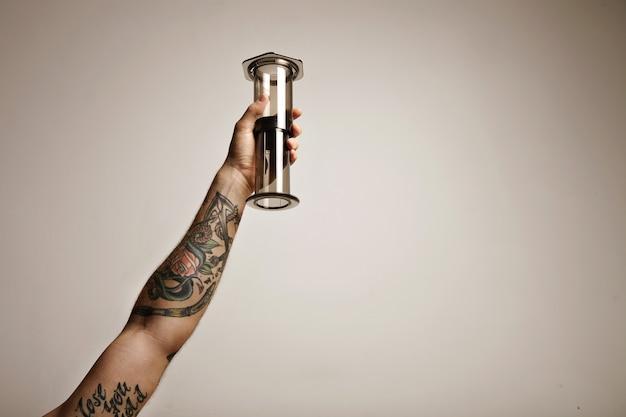 透明なライトグレーのエアロプレスの非伝統的なコーヒー醸造設備を持っている入れ墨の男の手の肖像画をクローズアップ白で隔離空中高く