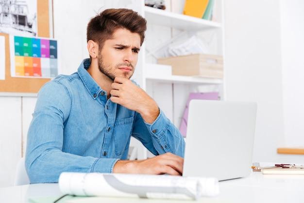 机に座って、オフィスでラップトップを使用して思いやりのある若いカジュアルなビジネスマンの肖像画をクローズアップ