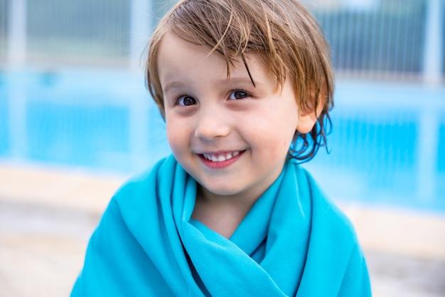 카메라를 보고 웃는 유아 소년의 초상화를 닫습니다. 여름 방학 동안 야외 수영장에서 긴 목욕을 한 후 수영 수건을 쓴 행복한 아이.
