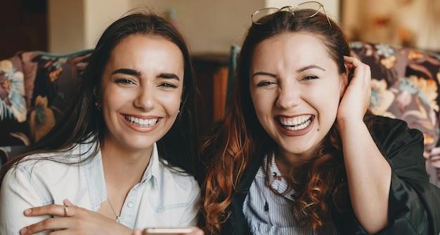 커피 숍에서 수업 후 커피를 마시는 동안 웃고 두 아름다운 젊은 여자 친구의 초상화를 닫습니다.