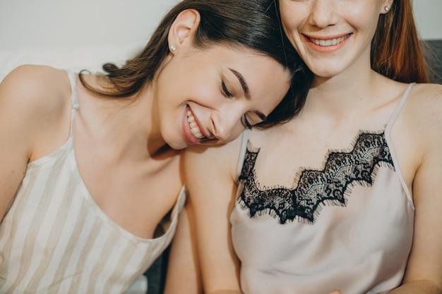 Крупным планом портрет двух милых сестер, смеющихся, развлекаясь в пижаме, где брюнетка, склонившая голову на плечо сестры.