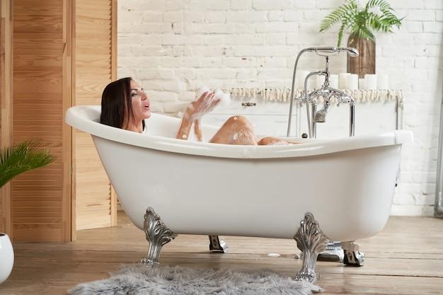 Портрет конца-вверх женщины ослабляя в жемчужной ванне