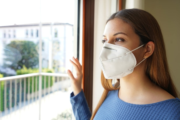 창문을 통해보고 얼굴 마스크를 쓰고 실내에 서있는 여자의 초상화를 닫습니다