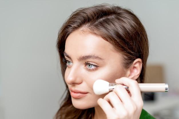 女性のクローズアップの肖像画は、彼女の顔に乾いた化粧品の色調のファンデーションを適用する化粧ブラシを使用しています