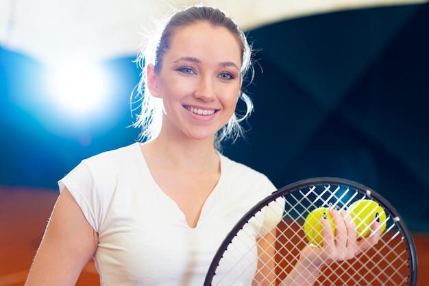 Крупным планом портрет молодой привлекательной женщины-теннисиста, держащего теннисную ракетку