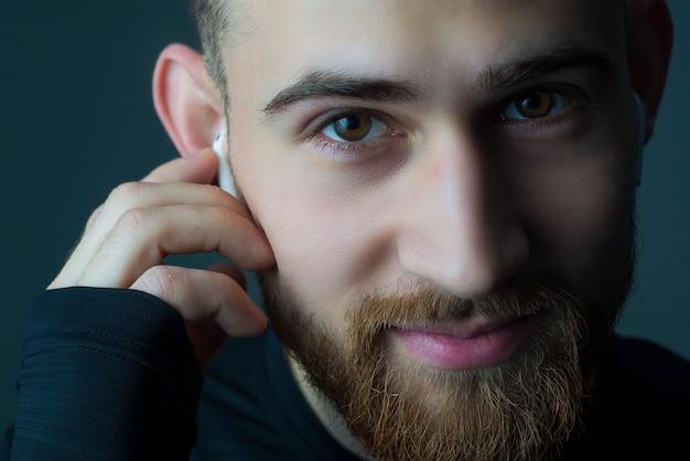 カメラを見て若いのひげを生やした男のクローズアップの肖像画