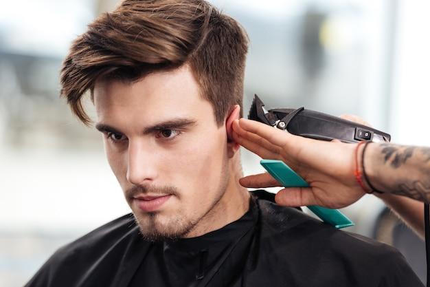 Макро портрет молодого бородатого мужчины, стриженного парикмахером, сидя в кресле в парикмахерской