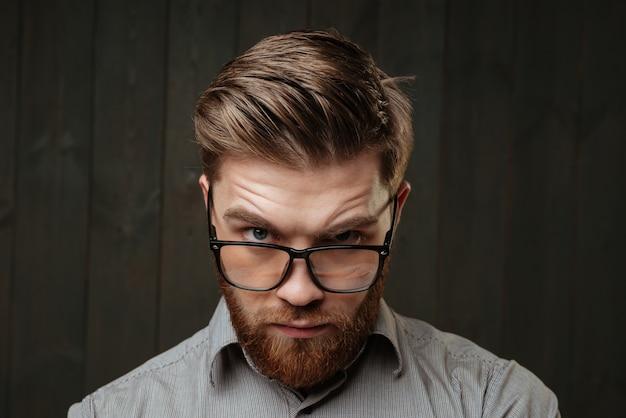 Крупным планом портрет молодого бородатого мужчины, смотрящего спереди поверх очков, изолированного на черной деревянной поверхности