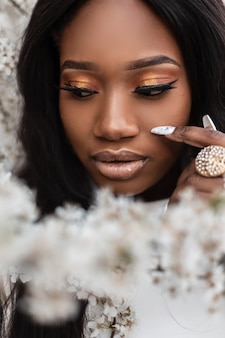 거리의 꽃 근처에 깨끗한 피부와 매니큐어를 가진 젊은 아름다운 흑인 여성의 클로즈업 초상화. 건강하고 아름다운 라이프스타일