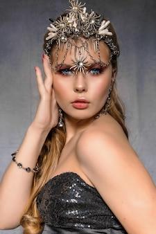 Крупным планом портрет молодой красивой блондинки в короне и бижутерии на сером фоне.