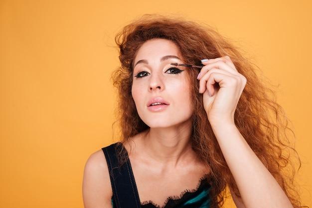 주황색으로 분리된 브러시로 눈에 마스카라 화장을 하는 빨간 머리를 한 아름다운 젊은 여성의 초상화를 클로즈업