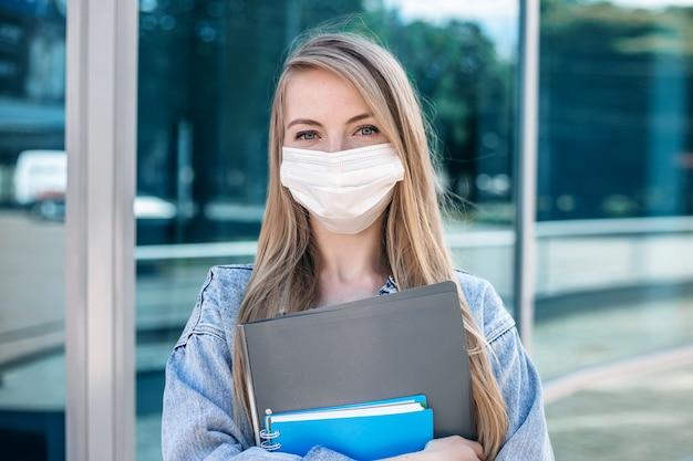 医療マスクで若いブロンドの女の子の肖像画を閉じる