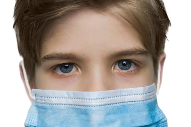 흰 벽에 의료 마스크에 어린 소년의 초상화를 닫습니다
