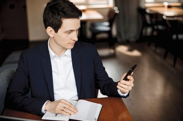 ノートブックに手を置いて机に座ってスマートフォンを見ている若い白人ビジネスマンの肖像画を閉じます。