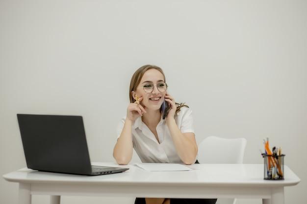 비즈니스 작업을 수행하기위한 준비가 그녀의 직장에서 젊은 자신감 여성 사무실 관리자의 클로즈업 초상화.