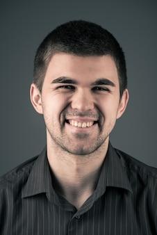 灰色の背景に若い感情的な陽気な黒髪の男のクローズアップの肖像画