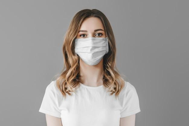 Крупным планом портрет молодой девушки в защитной медицинской маске, изолированной на белом